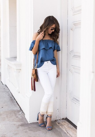 blouse blue off the shoulder top blue blue top ruffled top denim top white white jeans fringed bag blue sandals suede sandals off the shoulder summer summer outfits cropped bootcut white jeans shirt