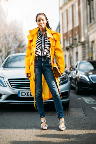 coat london fashion week 2017 fashion week 2017 fashion week streetstyle yellow yellow coat trench coat shirt printed shirt denim jeans blue jeans sandals sandal heels high heel sandals silver sandals bag yellow bag