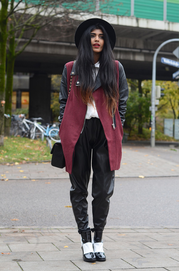 she wears fashion coat shoes blouse pants jewels patent boots leather pants black leather pants black pants baggy pants burgundy hat black hat winter outfits