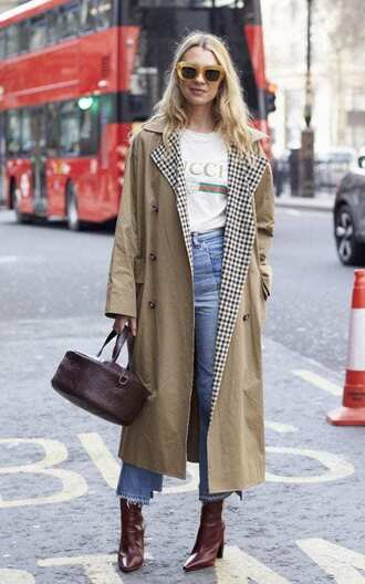 coat london fashion week 2017 fashion week 2017 fashion week streetstyle camel camel coat trench coat bag jeans denim blue jeans cropped jeans t-shirt white t-shirt logo tee boots red boots pointed boots high heels boots sunglasses yellow sunglasses gucci t-shirt